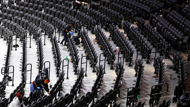 Workers clean the Wells Fargo Center after an NBA basketball game between the Philadelphia 76ers and the Detroit Pistons on March 11 in Philadelphia.