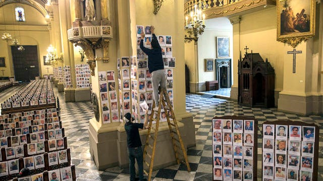 Workers stick portraits of people who died due to the COVID-19, inside the Cathedral, in Lima, Peru on June 13. Sunday's mass in Lima's cathedral with the presence of more than 4,000 portraits of the dead from COVID-19 is the first with these characteristics in the South American country where until Saturday more than 6,400 had died and more than 225,000 were infected.