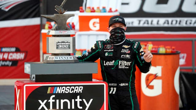 Justin Haley celebrates with the winner's trophy in Victory Lane after winning a NASCAR Xfinity auto race at Talladega Superspeedway in Talladega Ala., Saturday.