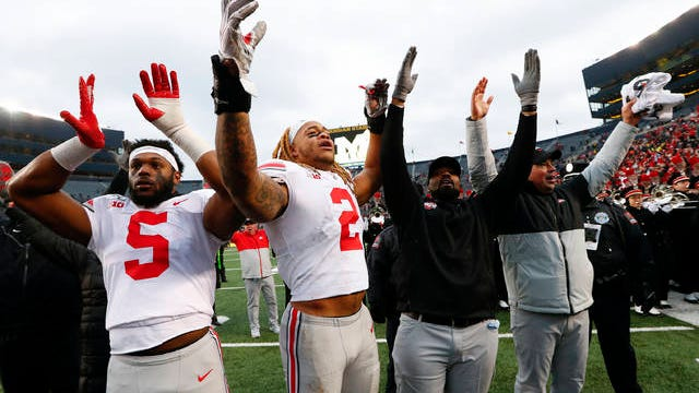 Ohio State's Baron Browning (5), Chase Young (2), linebackers coach Al Washington and head coach Ryan Day celebrate after a 56-27 win against Michigan after an NCAA college football game in Ann Arbor, Mich., Nov. 30, 2019.