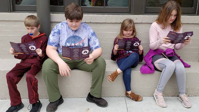 """Young participants review their passports for the annual """"Where's Maury the Mule"""" adventure."""