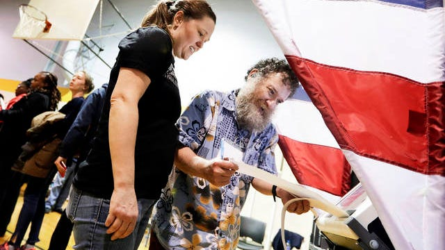 Voting machine operator David Schaefer, right, helps voter Kaitron Gordon with her ballot on Tennessee's Super Tuesday primary election at the Cleveland Park Community Center precinct on March 3 in Nashville. A judge has ruled that Super Tuesday polls will stay open later in Nashville after deadly overnight tornadoes delayed the start of voting in the city and rendered some of its polling places unusable.