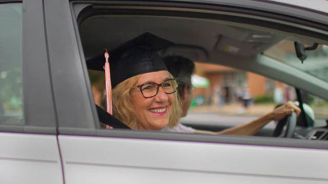 Christina Hooghkirk said she borrowed the cap and gown of her son for her own drive-through graduation ceremony at Columbia State Community College in Columbia, Tenn., on Saturday, June 27, 2020.