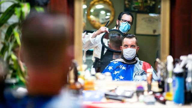 In this June 26 file photo, Barber Mike McAndrew holds a mirror as customer Rob Verrastro looks at his new haircut at Three Saints Barbershop and Shave Parlor in Jessup, Pa. Restaurants, retailers and salons are desperately trying to stay afloat as the U.S. economy reopens in fits and starts after months in a coronavirus lockdown. But billions of dollars allocated by Congress as a lifeline to those very businesses are about to be left on the table when the government's Paycheck Protection Program stops accepting applications for loans Tuesday, June 29.