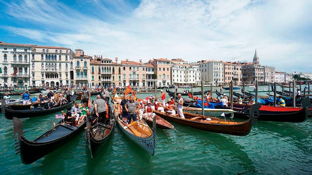 In this June 21 file photo, gondolas are lined up during the Vogada della Rinascita (Rowing of Rebirth) regatta, along Venice canals, Italy. European Union envoys are close to finalizing a list of countries whose citizens will be allowed back into Europe once it begins lifting coronavirus-linked restrictions. The United States appears almost certain not to make the list, as new infections surge and given that President Donald Trump has imposed a ban on European travelers.