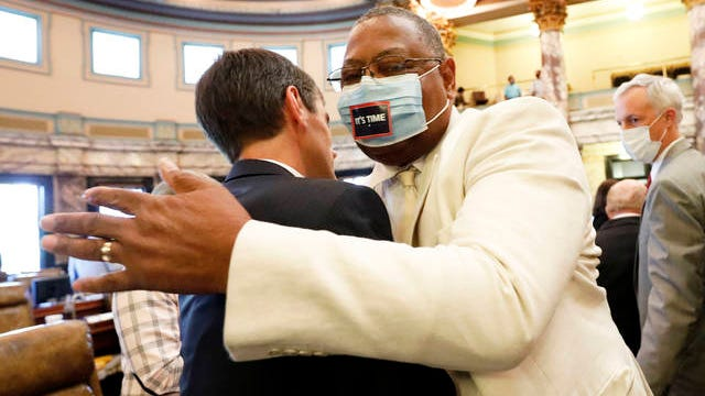 Sen. Briggs Hopson, left, R-Vicksburg, is hugged by Sen. Robert Jackson, D-Marks, after the Senate voted to change the state flag Sunday at the Capitol in Jackson, Miss. Hopson presented the bill to the body. Lawmakers in both chambers voted to surrender the Confederate battle emblem from their state flag. Republican Gov. Tate Reeves has said he will sign the bill.