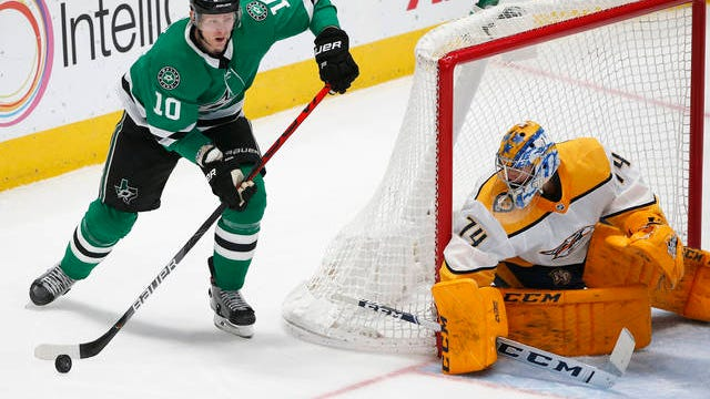 Dallas Stars right wing Corey Perry (10) moves the puck behind Predators goaltender Juuse Saros (74).
