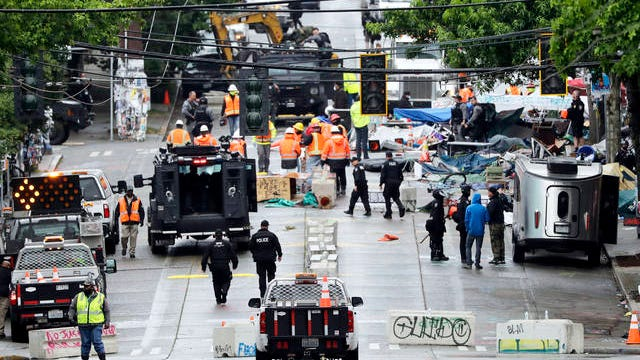 """Police and city workers fill a street occupied hours earlier by an encampment of protesters Wednesday in Seattle, where streets had been blocked off in an area demonstrators had occupied for weeks. Seattle police showed up in force earlier in the day at the """"occupied"""" protest zone, tore down demonstrators' tents and used bicycles to herd the protesters after the mayor ordered the area cleared following two fatal shootings in less than two weeks. The """"Capitol Hill Occupied Protest"""" zone was set up near downtown following the death of George Floyd while in police custody in Minneapolis."""