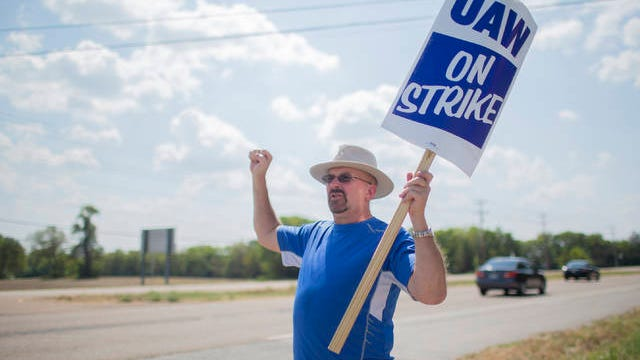 David Andersen holds his fist in the air as passing cars in Spring Hill the first full day of a national strike against GM on Sept. 16.