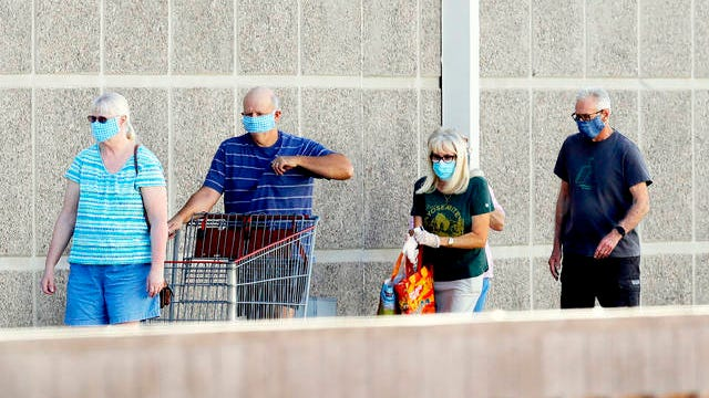 Customers wear masks as they wait to enter a store on June 17, 2020, in Tempe, Ariz. A group of Arizona medical professionals is urging Republican Gov. Doug Ducey to take steps like requiring masks in public to slow a major increase in new coronavirus cases that has made the state a national hot spot.