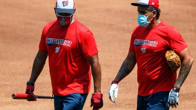 Washington Nationals' manager Dave Martinez, left, and bullpen coach Henry Blanco walk together during a baseball training camp workout at Nationals Stadium on July 5 in Washington.