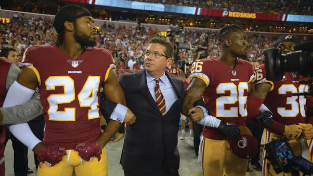 Redskins owner Daniel Snyder links arms with cornerbacks Josh Norman, left, and Bashaud Breeland during the national anthem on Sept. 24, 2017.