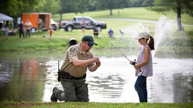 TWRA officer Ryne Goats assists 8-year-old Sophie Perusquina with her new fishing rod during a community outreach event at Woodland Park in Columbia on Wednesday.