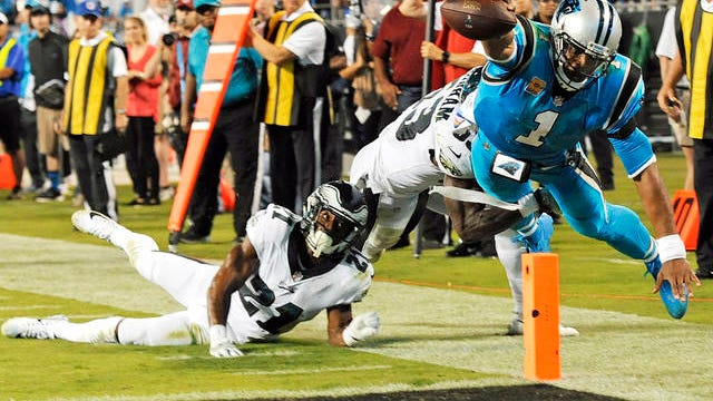 In this Oct. 12, 2017 file photo, Carolina Panthers' Cam Newton (1) dives short of the goal line as Philadelphia Eagles' Patrick Robinson (21) and Rodney McLeod (23) defend in the second half of an NFL football game in Charlotte, N.C. When the season starts, plenty of eyes will be focused on the New England Patriots as usual. Only this time it will be to see how 2015 NFL MVP Cam Newton fares replacing three-time MVP and six-time Super Bowl champion Tom Brady at quarterback.