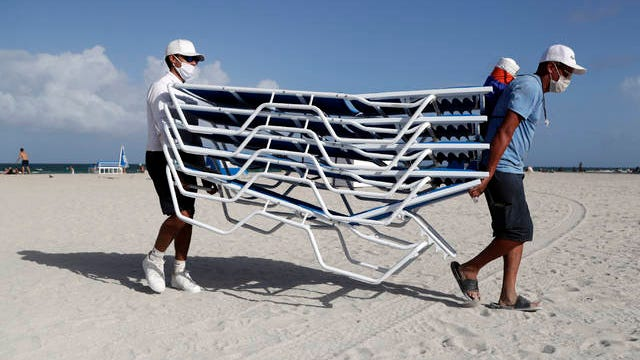 Workers remove chairs from the beach in preparation for Hurricane Isaias, Friday, in Miami Beach, Fla. Forecasters declared a hurricane warning for parts of the Florida coast Friday as Hurricane Isaias drenched the Bahamas on track for the U.S. East Coast.