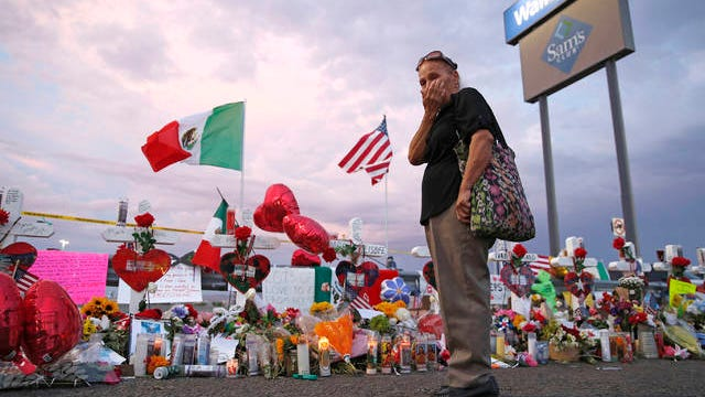 In this Aug. 6, 2019 file photo, Catalina Saenz wipes tears from her face as she visits a makeshift memorial near the scene of a mass shooting at a shopping complex in El Paso, Texas.