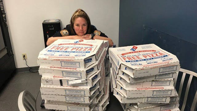 An officer with the Columbia Police Department poses with pizzas donated by a local Domino's