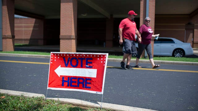 A couple holds hands after voting in the county general and state primary election at Spring Hill Middle School in Spring Hill, Tenn., on Thursday, Aug. 6, 2020.