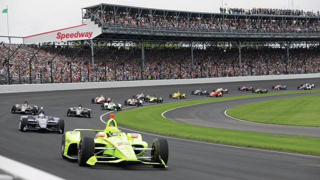 """In this 2019 file photo, Simon Pagenaud, of France, leads the field through the first turn on the start of the Indianapolis 500 IndyCar auto race at Indianapolis Motor Speedway in Indianapolis. Roger Penske has reversed course and decided not to allow fans at the Indianapolis 500 later this month. The 104th running of """"The Great American Race"""" will be the first without spectators, who showed up at Indianapolis Motor Speedway every year, even during the Great Depression."""