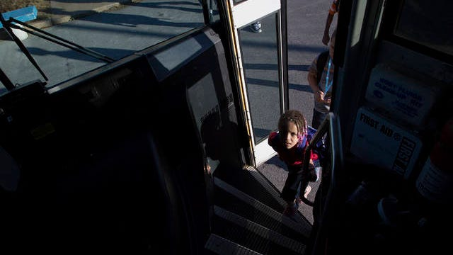 Six-year-old Joseph Brown Elementary School first grader Teiona Williamson climbs onto her school bus after dismissal on Wednesday, Nov. 20, 2016.