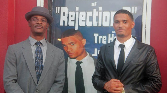 """Tre Harper, right, is shown here with his father, Theron Harper, left, outside the Constantine Theater in downtown Pawhuska, and in front of the publicity poster for """"Rejection 2: Darrin's Revenge,"""" a movie in which Tre Harper, a recent Pawhuska High School graduate, has a supporting role. Robert Smith/Journal-Capital"""