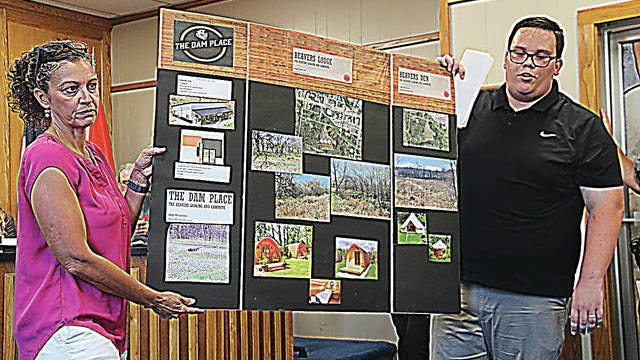 Tara Hendren, left, and Hunter Hansen, right, help to make a presentation to the Pawhuska City Council about a new business venture that Help Works is pursuing. In the photo, Hendren and Hansen are holding a visual aid where members of the council's audience can see it. Robert Smith/Journal-Capital