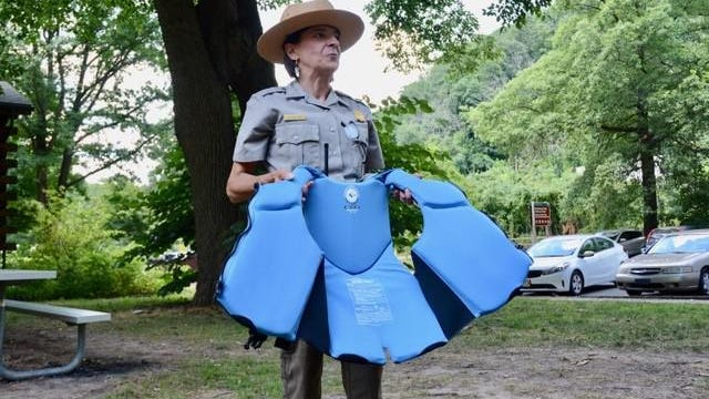 Kathleen Sandt of the National Park Service demonstrates how to properly wear a life jacket. There have been five drownings in just about six weeks along the Delaware River in the Delaware Water Gap National Recreation Area this summer.