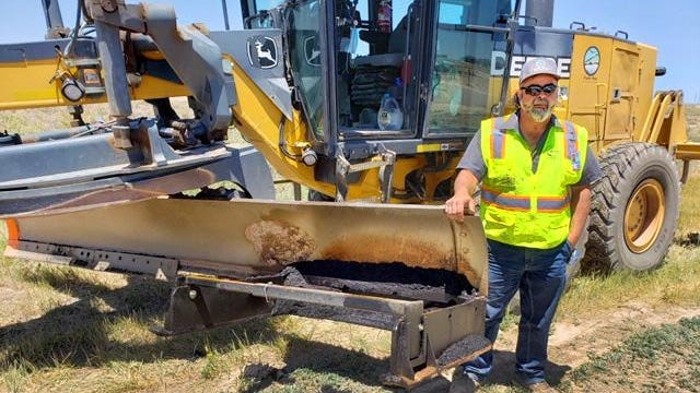 Inventor Albert Martinez stands next to the grader blade attachment that he designed and built to help road crews edge roads in preparation for chip seal improvements.