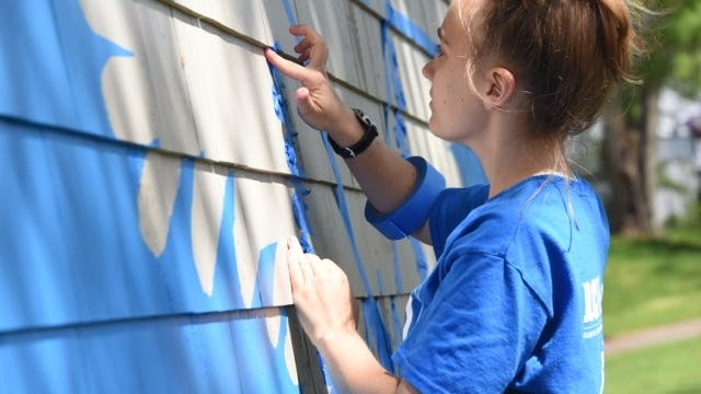 Annabelle O'Reilly works on her wing mural in Hopedale.