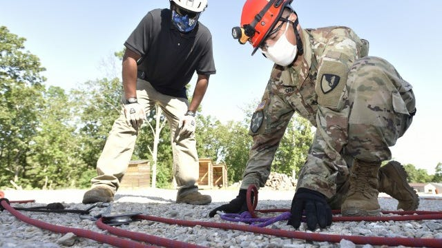 Staff Sgt. Harry Cruz, a Construction Engineer Supervisor at Fort Hood, Texas, demonstrates the building of a 9:1 compound mechanical advantage system while Kito Perry, an Urban Search and Rescue course training instructor, provides technical assistance.