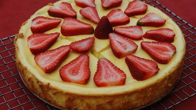 A layer of sticky sweet rhubarb is in the middle of this cheesecake, which is topped off with strawberries.
