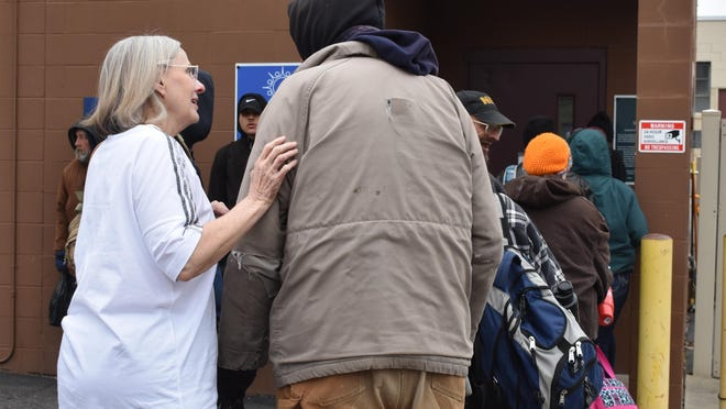 """Share the Warmth of Lenawee County President Helen Henricks, at left, speaks with a guest of the homeless shelter located in Adrian, in March 2020. Share the Warmth was the beneficiary of $431.25 in donation money from Cadmus Presbyterian Church's annual """"House of Change"""" fundraiser, which collects money for a local agency each August through November."""
