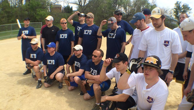 """Members of the Iowa City Police Department (left) and the Delta Tau Delta fraternity strike a pose before the first """"Sluggin' for a Solution"""" charitable softball game Saturday afternoon in Iowa City."""