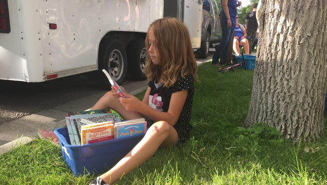Audrina digs through a blue bin of Junie B. Jones books, searching for the perfect read.