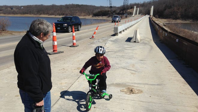 Maddox Schwalm-Bell, 4, was the first person Saturday to ride across the newly completed trail bridge next to the Mehaffey Bridge over the Iowa River and Coralville Lake in rural Johnson County. The bridge was open to foot and bike traffic temporarily. On Monday, the trail bridge will be used for single-lane vehicle traffic while the rest of the bridge is worked on.