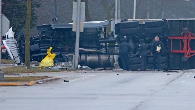 Police investigate near a turned over semitrailer truck at the scene of a fatal car accident that included at least one vehicle and a semi truck at the intersection of W. Good Hope Road and N. 43rd St. on Thursday.