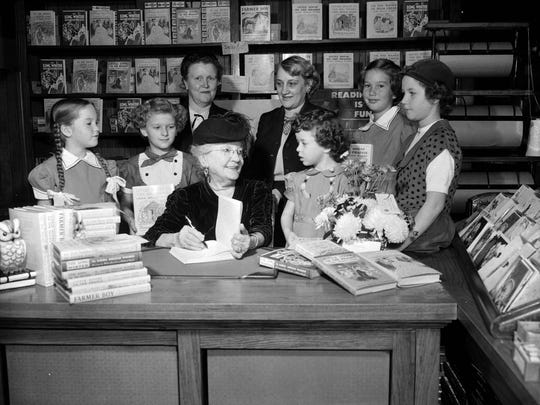 Laura Ingalls Wilder signing books at the Brown Brothers Book Store in Springfield. Mrs. L.D. Lichty, Mrs. Leslie E. Hatfield, Jane Weigel, Patty Sue Patterson, Linda Robertson, Ann Weigel, and Patsy Curbow are identified in the image. Published in the Leader & Press on November 17, 1952.