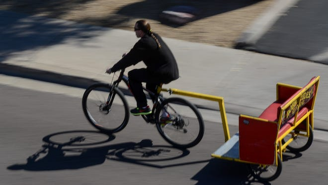A pedicab driver searches for fares during a spring training game on Saturday, Feb. 23, 2013, in Scottsdale.