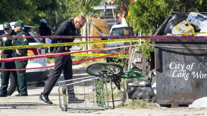 A detective looks for evidence in an alley between South F and G Streets after three people were shot in Lake Worth Beach Sunday afternoon, September 29, 2019. According to the Palm Beach County Sheriffs Office, one man was killed and two injured.