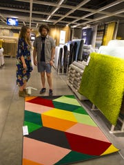 Leah Jones and Broc Riblets of Milford look at rugs