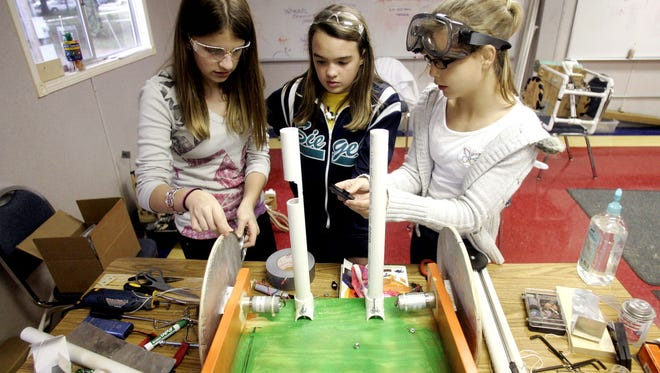 Former Discovery School students Olivia Richie, from left, DeLaina McDonald, Morgan Murdock prepare for the annual Music City BEST Robotics Competition in 2011.