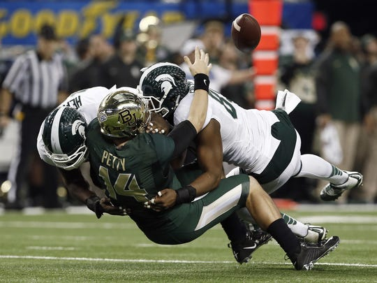 Baylor quarterback Bryce Petty (14) fumbles as Michigan State defensive linemen Joel Heath, left, and Shilique Calhoun (89) make the sack during the 2015 Cotton Bowl. Calhoun led the Spartans that season with eight sacks, and now plays for the Oakland Raiders.