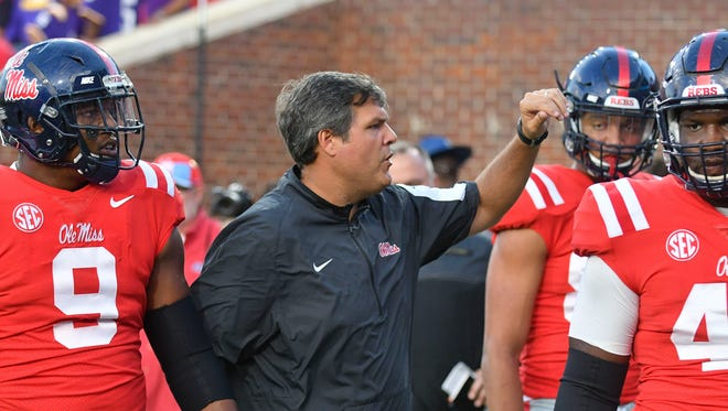 Ole Miss head coach Matt Luke talks with players during warm ups before a game against the LSU Tigers at Vaught-Hemingway Stadium.