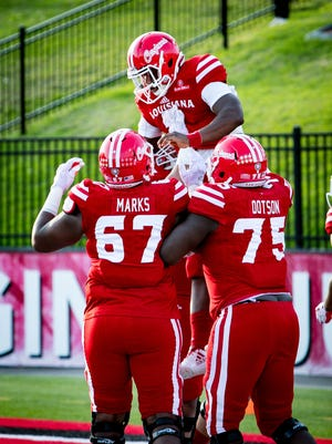 UL offensive linemen Ken Marks, left, and Kevin Dotson lift teammate Dion Ray after the Wildcat quarterback's touchdown in the Ragin' Cajuns' win over New Mexico State last Saturday at Cajun Field in Lafayette, Louisiana on November 18, 2017.