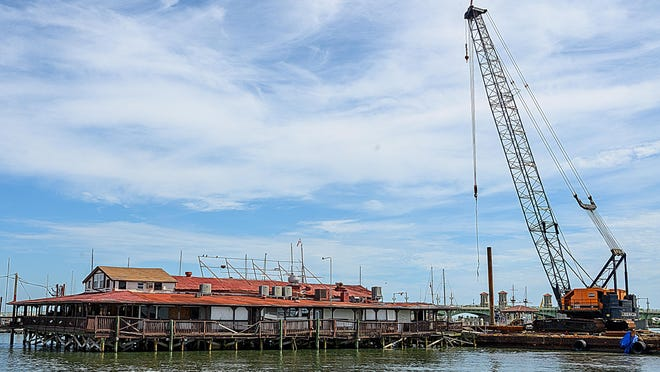 A crane being used in the demolition of the former Santa Maria restaurant in downtown St. Augustine sits on a barge next to the building on Thursday. It is expected to take two to three weeks to demolish the building, which sits over the Matanzas River south of the Bridge of Lions and the St. Augustine Municipal Marina.