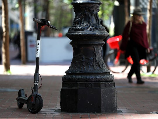 A Bird scooter sits parked on a street corner on April 17, 2018, in San Francisco.