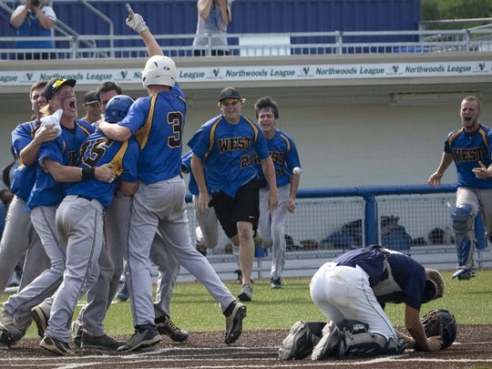 New Berlin West players celebrate the game-winning run on a suicide squeeze bunt by Mike Philips in the state semifinal against Kettle Moraine.