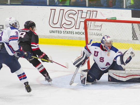 Chicago's Lucas Michaud (No. 8) watches as NTDP U18 goalie Jake Oettinger snares his shot Tuesday night. At left for the U18s is Michael Campoli (No. 3).