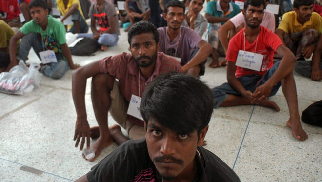 Rohingya migrants sit on the floor at the authority's district office of Rattaphum, Songkla province, southern Thailand, as they were found abandoned in Khao Kaew mountain near the Thai-Malaysia border, Saturday, May 9, 2015.