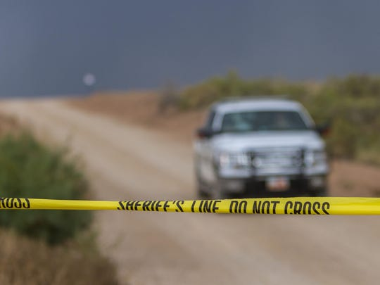 A sheriff's vehicle leaves the scene of a plane crash at Quichapa Lake outside of Cedar City, Monday, Oct. 5, 2015.